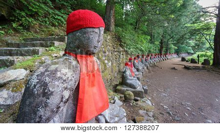 Wide angle perspective view of moss covered statues of Jizo in Nikko, Japan. Side view