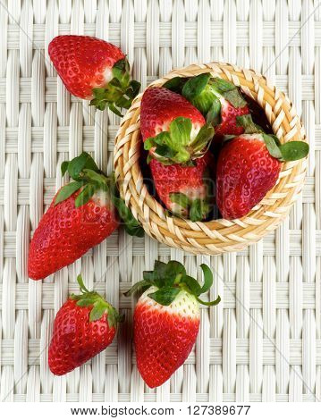 Arrangement of Fresh Ripe Strawberries in Wicker Bowl closeup on White Wicker background. Top View