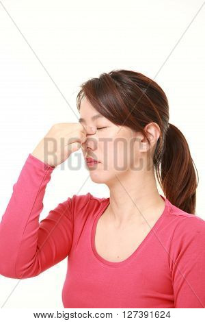Japanese woman suffers from Asthenopia on white background