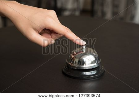 hand push service bell on wooden table.