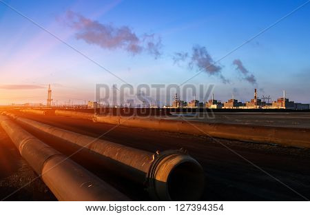 Nuclear energy and pollution. The huge plant on the background of lying pipes at sunset.