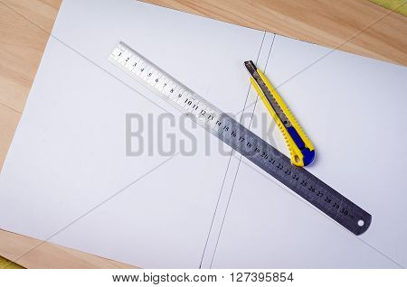 paper cutter and ruler on wood background