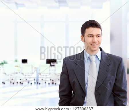 Happy young caucasian businessman in suit and tie at bright office. Standing, smiling, copyspace.