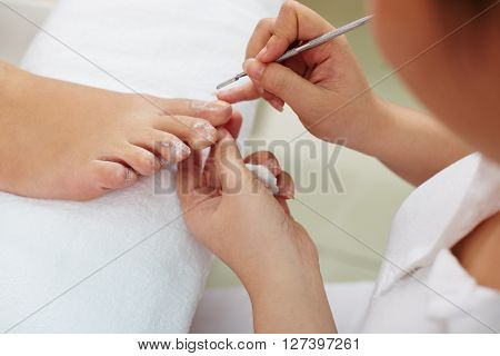 Woman receiving pedicure by beautician in nail salon