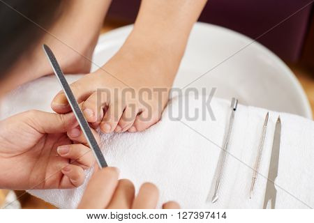Close-ip of pedicurist filing toenails of female client