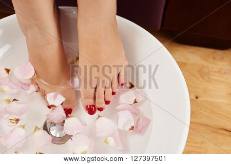 Woman having bath with rose petals for her feet