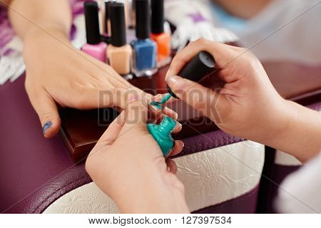 Close-up image of manicurist painting nails green