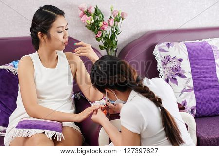 Pretty Asian woman blowing on her nails to make them dry faster