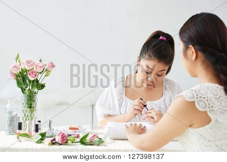 Young Asian manicurist working with client in beauty salon