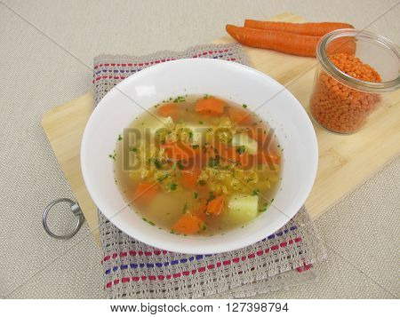 Broth with lentils, potatoes and carrots in soup bowl