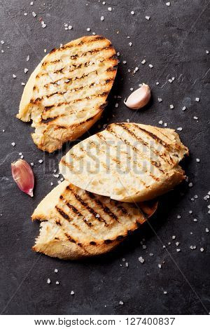 Toast bread with salt and garlic on stone table. Top view