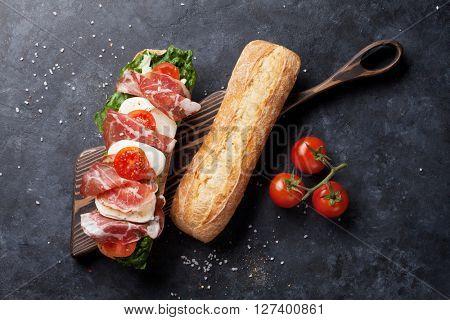 Ciabatta sandwich with romaine salad, prosciutto and mozzarella cheese on stone table. Top view