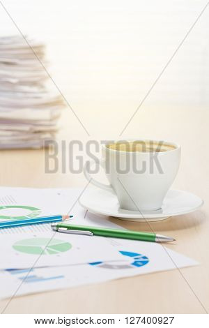 Office workplace with coffee cup, supplies and reports on wood desk table in front of window with blinds. View with copy space