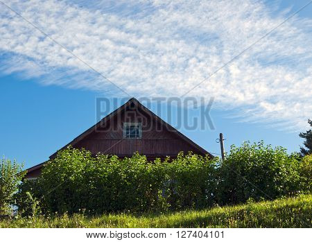 Rustic wooden house on a background of blue sky