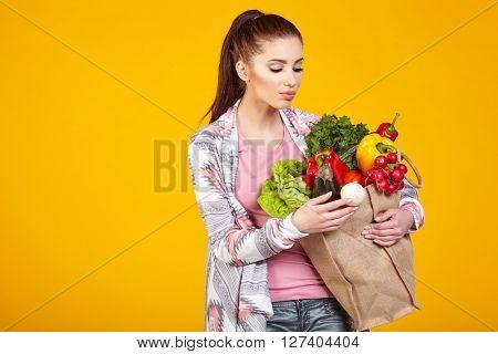 woman with green vegan food. Shopping bag. surprise emotion. Yellow background.