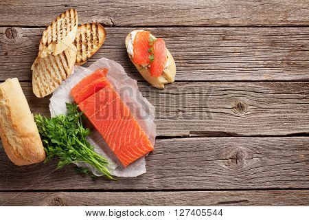 Sandwich toast with salmon cooking on wooden background. Top view with copy space