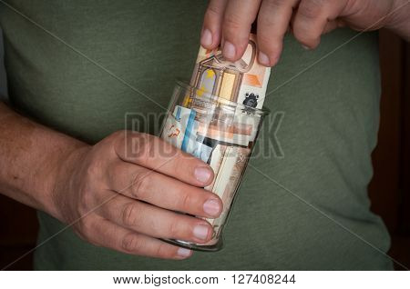 a man holds a glass jar with money. And puts or gets money