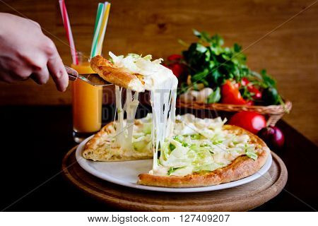 The slice of pizza with melted cheese in caffe