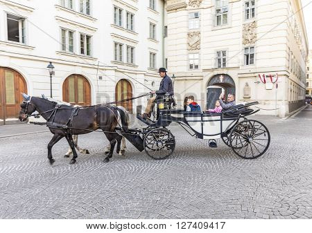 Tourists Enjoy Horse-drawn Carriage Or Fiaker
