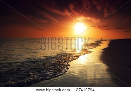 Sunset and surf on tropical beach