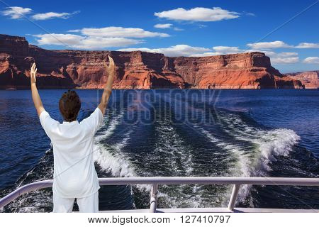 Middle-aged woman in white at the stern of the ship admiring the beauty of nature. Artificial lake Powell on the Colorado River, USA.