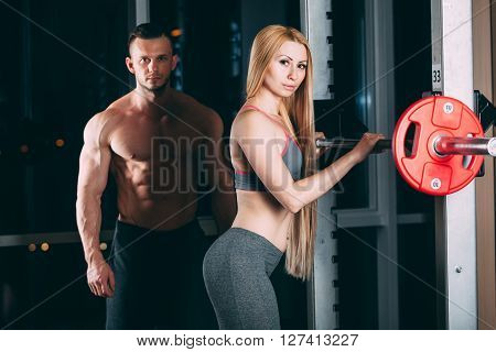 Young couple exercising in gym with weights the man seems to be the personal trainer. ** Note: Soft Focus at 100%, best at smaller sizes