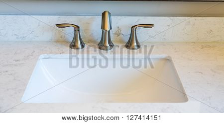 A Brushed Nickel faucets on Marble Vanity