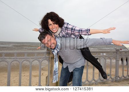 Man Giving His Smiling Wife A Piggy Back At The Beach On A Spring Day