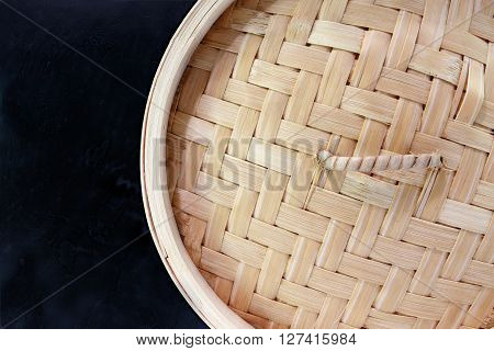 Chinese style bamboo steamer top view against dark background