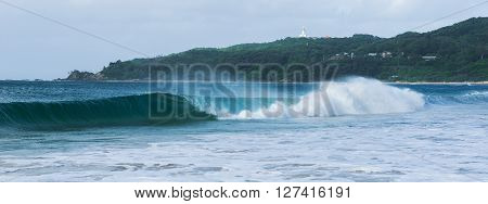 Byron Bay beach and waves in New South Wales, Australia with Cape Byron lighthouse in the background.