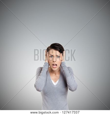 Confused woman puts her hands on the head, isolated on grey