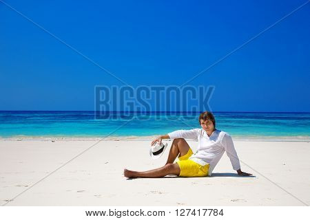 Successful Handsome Man In Hat Resting On Exotic Seashore With Blue Water And White Sand. Summer Bea