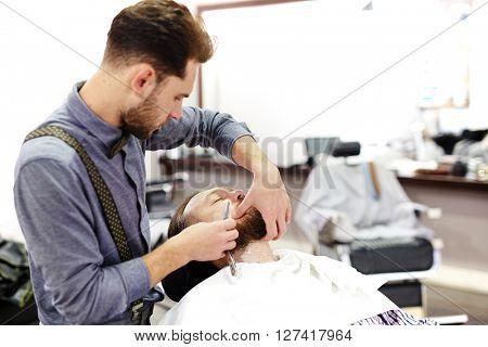 Shaving beard of client