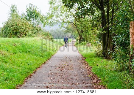 ESSEN GERMANY - SEPTEMBER 30 2014: Group of older men cycling on the promenade of the river Ruhr near Essen Werden towards Kettwig.