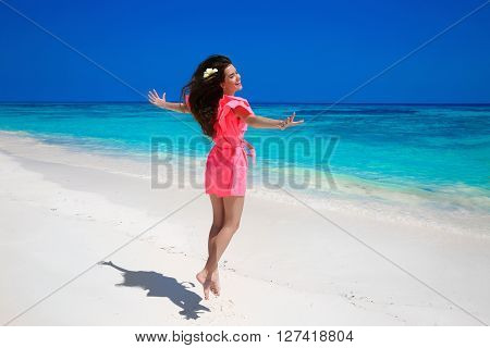 Fitness. Beautiful Happy Woman Jumping On Exotic Sea, Brunette Smiling Girl In Red Dress Enjoying On
