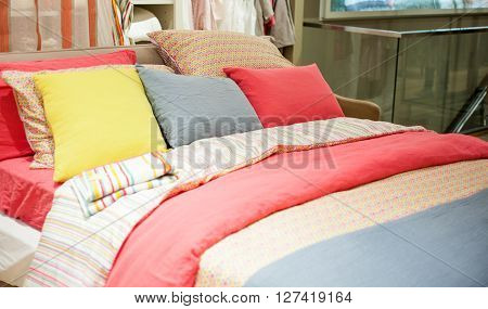 View of colorful pillows on a bed