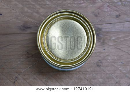 tin can with lid opener on wooden table