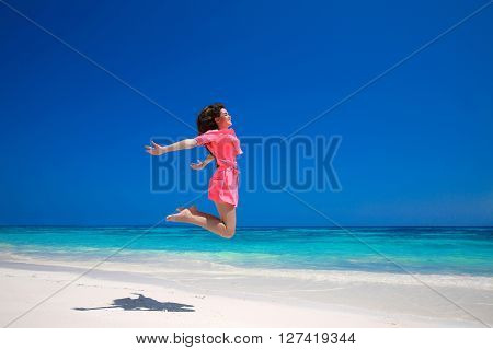 Summer Enjoyment. Happy Young Woman Jumping On The Sea, Brunette Smiling Girl In Red Dress Running O