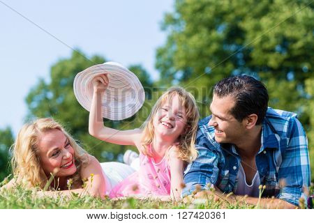 Happy Family, lying on grass, cute little girl in the middle