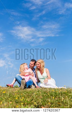 Parents and daughter sitting on grass, total view, centred, centered