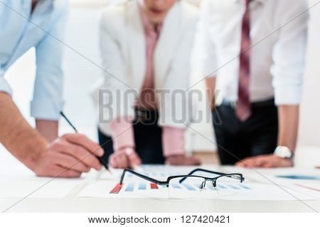 Business people analyzing financial data - glasses on graph, symbol for focus and detail