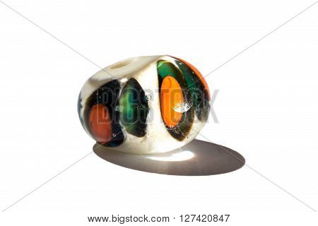 Hand made green and orange glass bead on white background