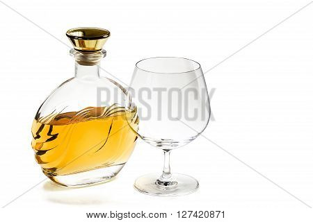 Bottle of brandy and empty snifter on white background