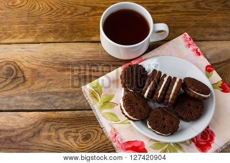 Chocolate cookies sandviches and cup of tea. Sweet dessert. Homemade biscuit. Chocolate sandviche. Breakfast cookie