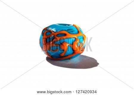 Hand made orange and blue glass bead on white background