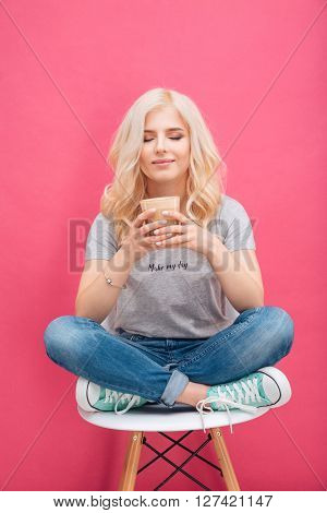 Happy woman drinking cappuccino over pink background