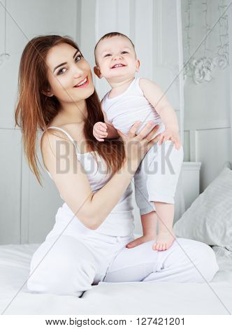 young mother and her one year old son in bed at home