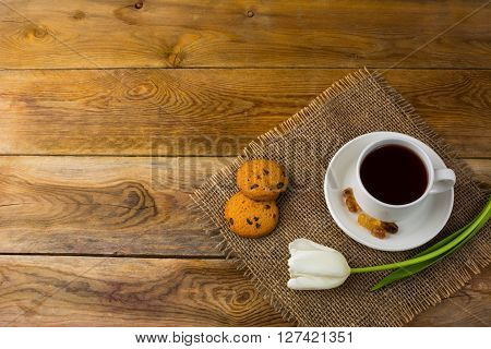 Tea cup and white tulip on sackcloth top view copy space. Cup of tea. Tea cup. Tea party. Breakfast tea