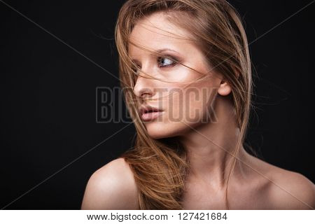 Beauty portrait of a lovely woman with fresh skin looking away over black background