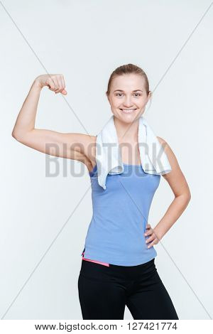Happy fit woman showing her biceps isolated on a white background